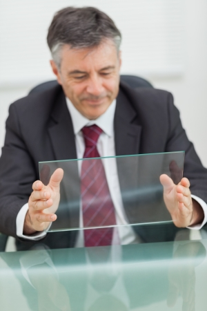 Smiling business man holding a virtual screen on his desk in his office photo