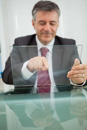 Smiling man touching on a virtual screen on his desk in his office photo