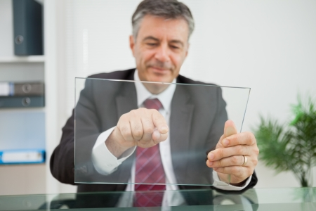 Happy man pointing on his virtual screen on his desk in his office photo