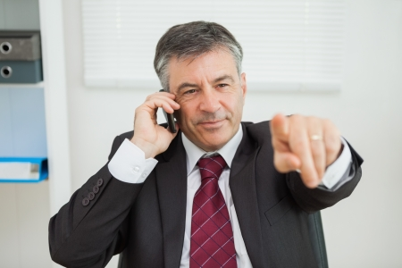 Businessman phoning and pointing sitting at his desk in his office photo