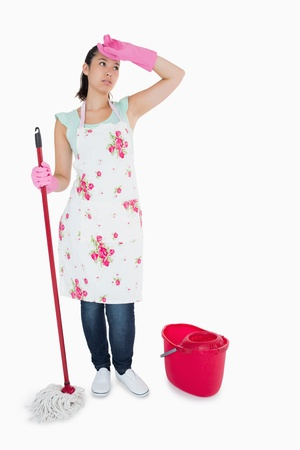 Tired woman cleaning the floor with mop and bucket photo