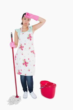 Discouraged woman cleaning the floor with mop and bucket photo