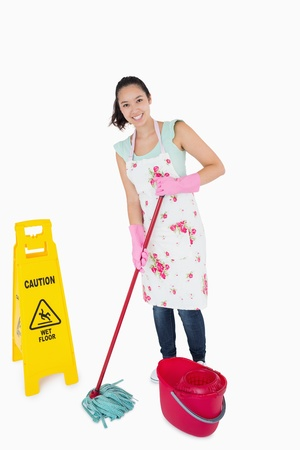 Woman cleaning near a caution wet floor sign photo