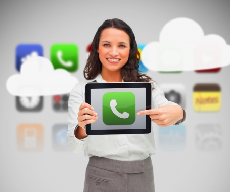 Woman holding tablet pc pointing to phone symbol on background of various phone applications and clouds photo