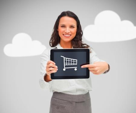 Businesswoman holding a tablet pc avec le symbole du shopping et souriant Banque d'images