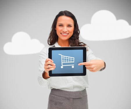 Woman standing while holding a digital tablet with shopping app on grey cloud background photo