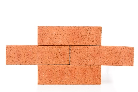 out of context: Four clay bricks building a wall against a white background Stock Photo