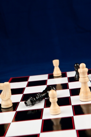 Black queen lying at the chessboard while white chessmen surrounding it photo