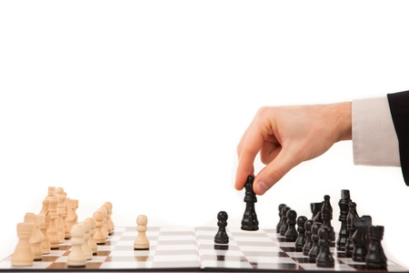 out of context: Hand moving a black chessman against white background Stock Photo