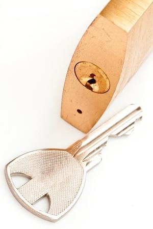 shutting: Key lying next to padlock against white background Stock Photo