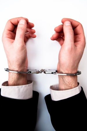 handcuffing: Hands handcuffed against white background Stock Photo