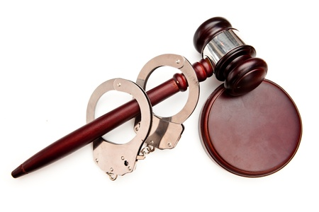 Gavel and handcuffs against white background