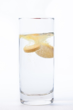Vitamin tablet dissoving in glass of water photo