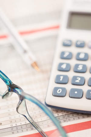 out of context: Shot of calculator and glasses lying on statistic table Stock Photo