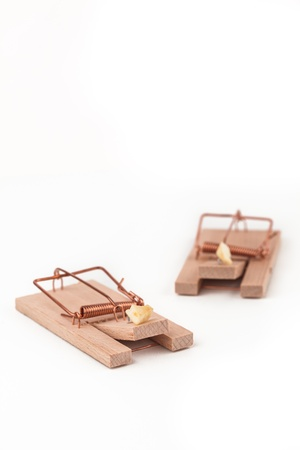 Two mousetraps with cheese on white background photo