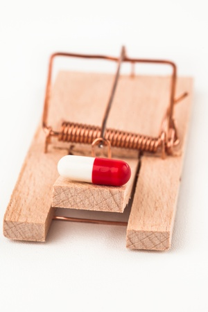 Pill in a mousetrap on white background photo