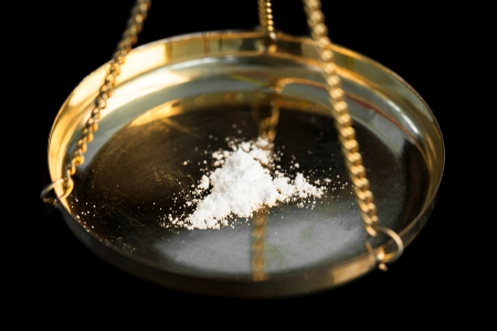 illegal substance: White illegal substance being weighed on black background