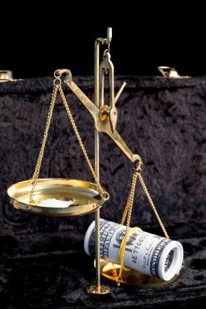 weighing scales: Bilance confronto mazzetta di dollari e la pila di bianco droga illegale