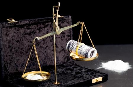 weighing scales: Bilance con mazzetta di dollari e droga in polvere bianca, accanto grande mucchio di droga