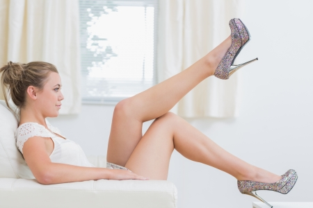 Woman trying new high heels in living room photo