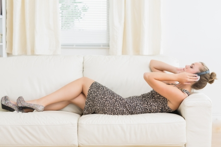 Woman listening to music on the sofa while relaxing photo