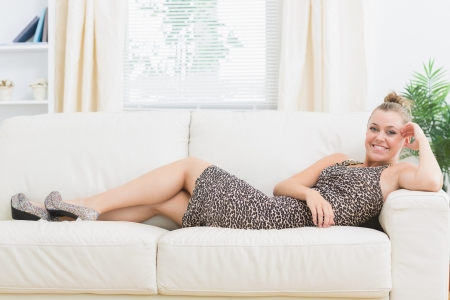 woman on couch: Woman with high heels and dress smiling and lying on the sofa