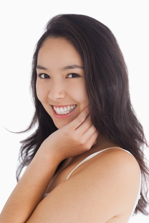long faced: Female beauty smiling while touching her skin Stock Photo