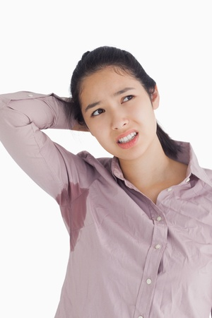 perspiration: Embarassing woman with sweat patches looking away