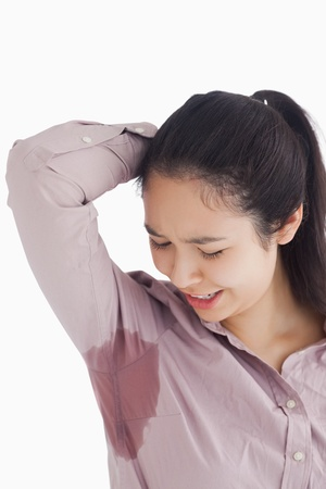 perspiring: Distressed woman looking at sweat patches Stock Photo