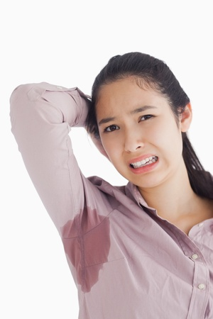 Woman appalled by her sweat patches on white background Stock Photo