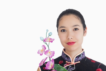 Woman holding an orchid while smiling and wearing a kimono photo