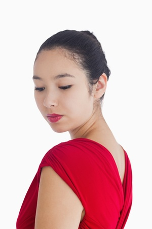 Woman looking over her shoulder in red dress smiling gently photo
