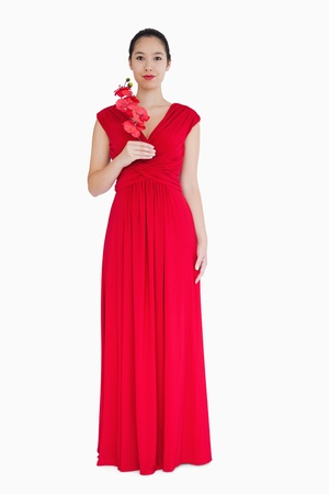 red evening: Smiling woman in red evening gown with orchids