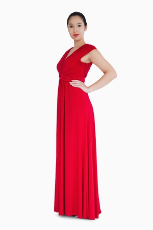 evening gown: Smiling woman standing a red evening gown Stock Photo