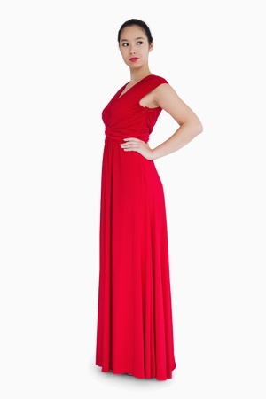 Woman standing in red dress with her hands on her hips Stock Photo