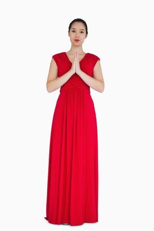 evening gown: Woman standing in red evening gown with hands together