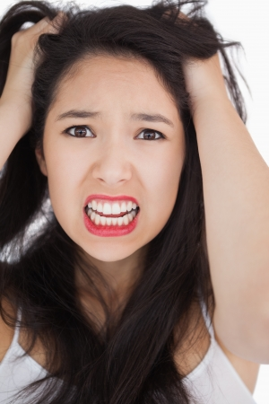 outraged: Woman looking shocked and angry against white background
