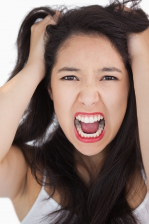 outraged: Woman screaming and pulling her hair out on white background Stock Photo