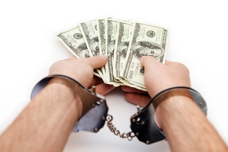 Hands wearing handcuffs holding fan of hundred dollar bills Stock Photo - 16076024