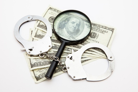 Magnifying glass dollars and handcuffs lying against white background photo