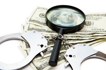 Handcuffs dollars bills and a magnifying glass on white background photo