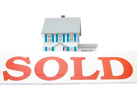 abode: Sold sign in front of house on white background