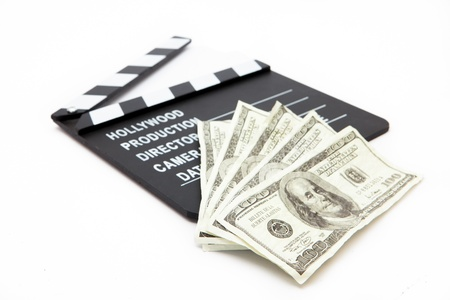 Film slate and money lying against white background photo
