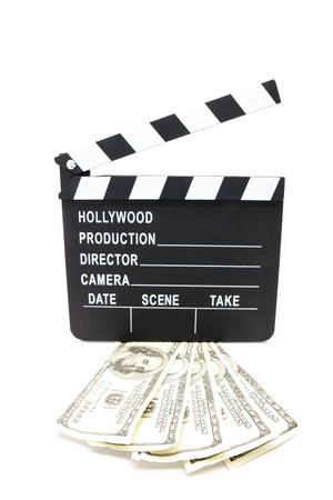 Fanned out dollar bills under film slate on white background photo