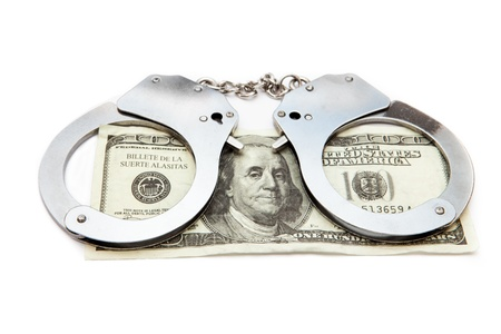 Handcuffs and money against white background photo