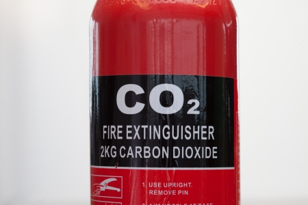 pressurized: Red carbon dioxide fire extinguisher close up