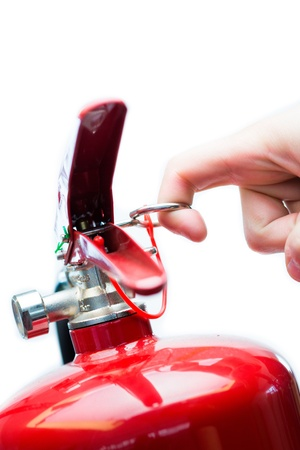 Hand pulling safety pin from red fire extinguisher photo