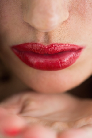 Close-up of woman with red lips sending an air kiss photo