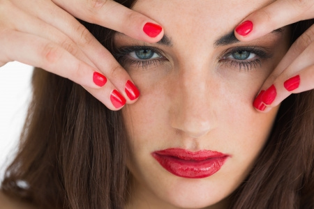 Brunette woman touching her eyebrows while having red lips and red nails photo