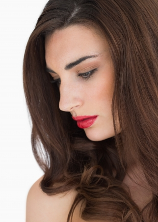 Woman with long hair and red lips and looking away photo